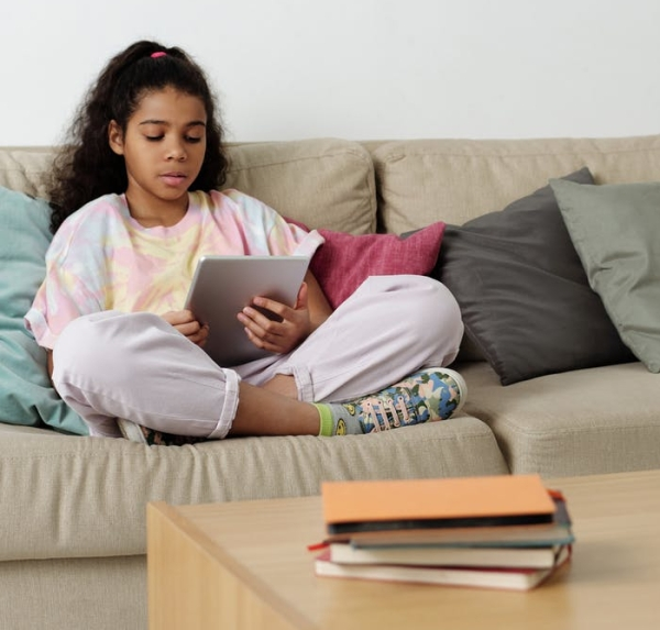 photo of girl sitting on sofa while using tablet